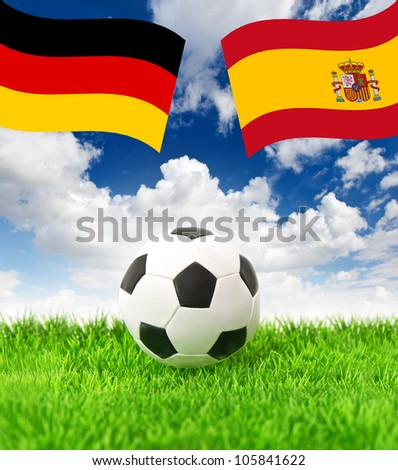 soccer ball on green grass and national flags of germany and spain over dramatic blue sky