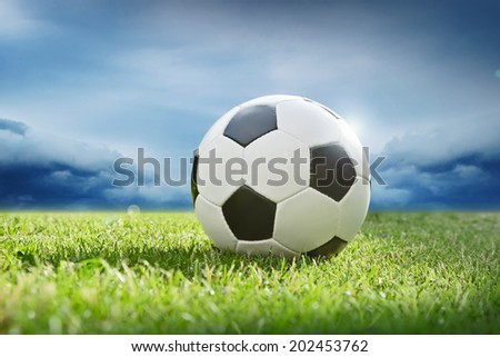 Soccer ball on green grass before the storm - stock photo