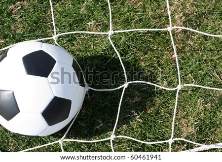 Soccer ball on the net with room for copy - stock photo