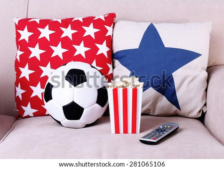 Soccer ball, remote control and box of popcorn on comfortable sofa, indoors - stock photo