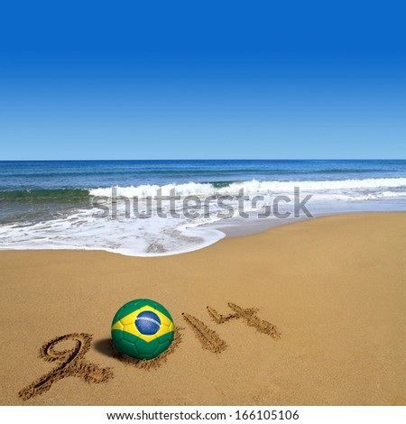 Soccer ball with Brazilian flag and 2014 on beach - stock photo