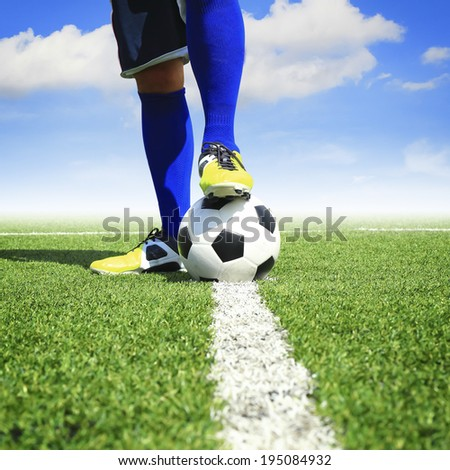 soccer ball with feet player on the football field - stock photo