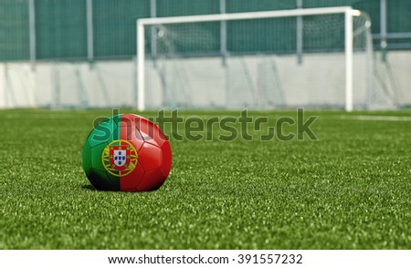 Soccer ball with the flag from Portugal on the green field