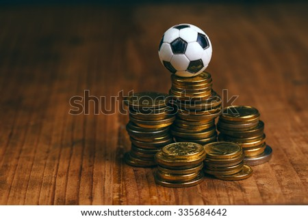 Soccer bet concept with small football on top of coin stack, making money by predicting sport results. - stock photo