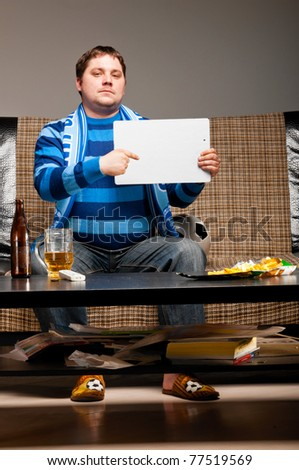 soccer fan is sitting on sofa with beer at home and holding blank cardboard - stock photo