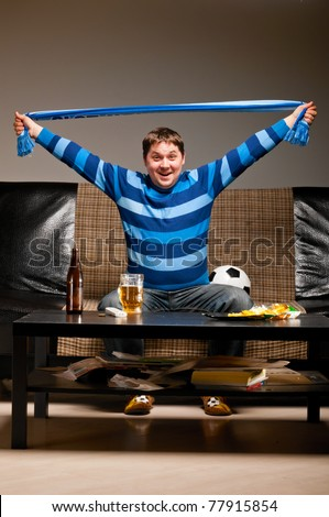 soccer fan is sitting on sofa with scarf in hands with beer at home - stock photo
