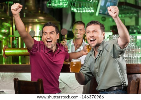 Soccer fans at the bar. Two happy football fans cheering at bar and drinking beer while bartender serving beer at the background - stock photo