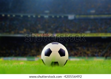 soccer field and stadium with fans the night before the match, Soccer ball or football, Soccer stadium, soccer ball on green stadium, arena in night illuminated bright spotlights, soccer arena. - stock photo