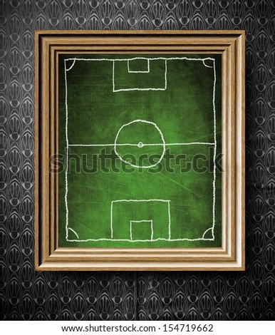 Soccer field symbol chalkboard in old wooden frame on vintage wall - stock photo