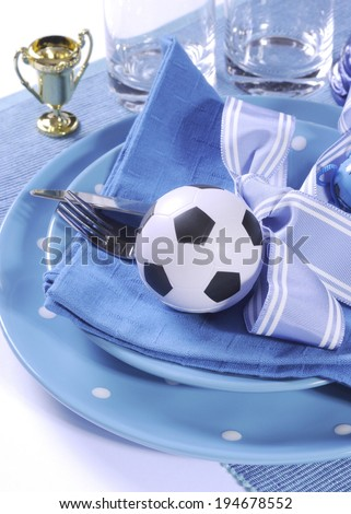 Soccer football celebration party table setting with pates, cutlery, glasses, trophy, soccer ball and decorations in blue and white team colors. - stock photo
