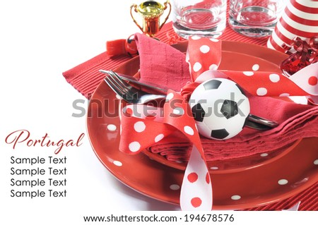 Soccer football celebration party table setting with pates, cutlery, glasses, trophy, soccer ball and decorations in red and white team colors. - stock photo