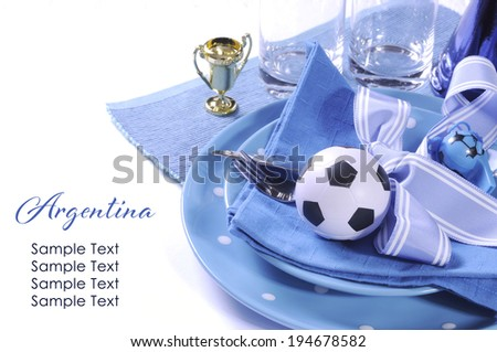 Soccer football celebration party table setting with pates, cutlery, glasses, trophy, soccer ball and decorations in blue and white team colors with copy space. - stock photo