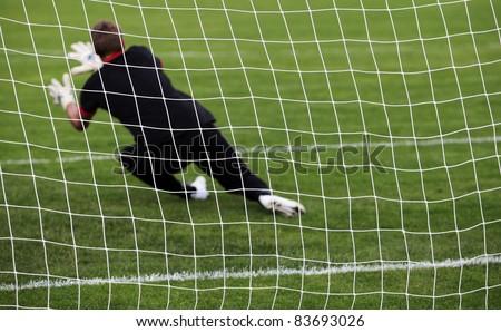 Soccer football goalkeeper making diving save - stock photo