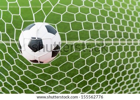 Soccer football in goal net with green grass field - stock photo