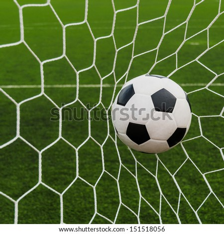Soccer football in Goal net with green grass field. For sport concept. - stock photo
