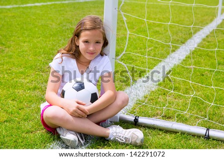Soccer football kid girl relaxed on grass lawn with ball - stock photo