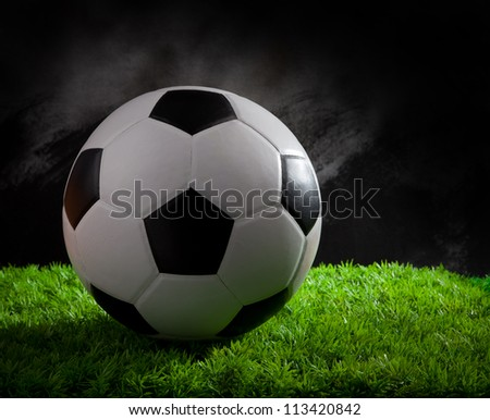 soccer football on green grass studio light - stock photo