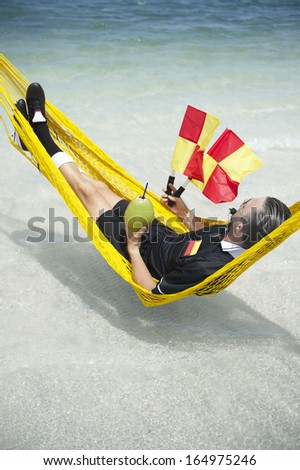 Soccer football referee takes a break from the match to relax at the beach in hammock with coconut - stock photo