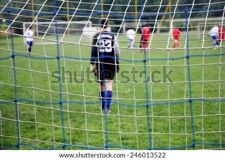 Soccer goal mesh with football players in action background soft focus - stock photo