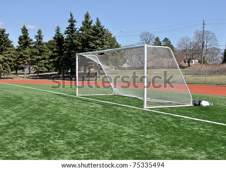 Soccer Goal posts on astroturf field under blue sky - stock photo