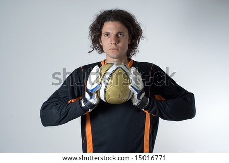 Soccer goalie holds a soccer ball with his goalie gloves and has a serious expression on his face. Horizontally framed photograph - stock photo