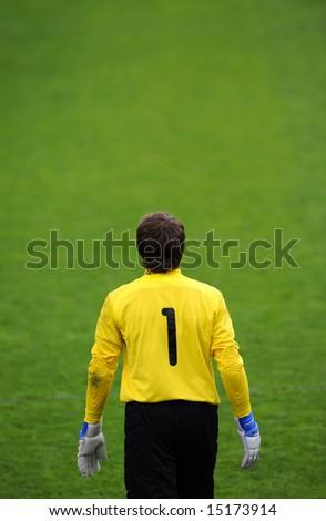 Soccer goalie waits for ball. Shot from behind goalie. - stock photo