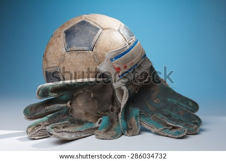 Soccer goalkeeper's gloves and the ball, with blue color in the background - stock photo