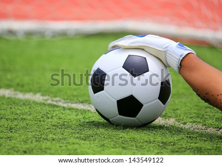 Soccer goalkeeper's hands reaching for the ball - stock photo