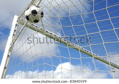 soccer gool, the ball into the net against blue sky - stock photo