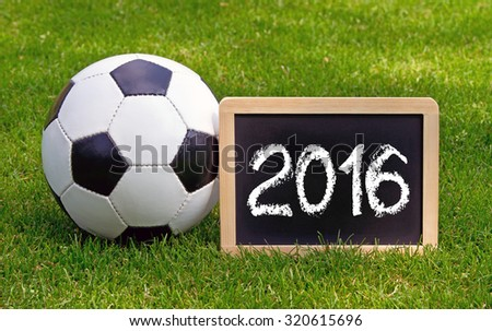 Soccer in 2016 - leather ball with chalkboard on green grass - stock photo
