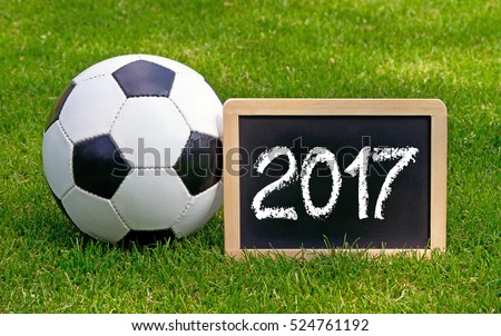 Soccer 2017 - leather ball with wooden chalkboard on green grass background