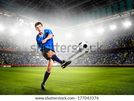 soccer or football player is kicking ball on stadium - stock photo