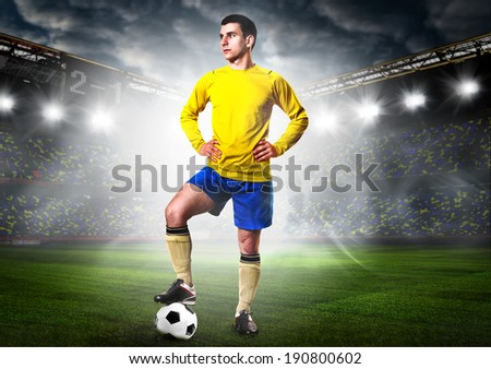 soccer or football player is standing on stadium - stock photo