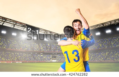 soccer or football players are celebrating goal on stadium