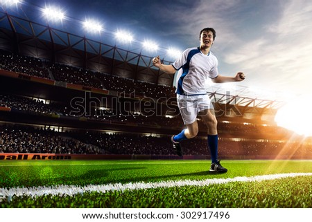 Soccer player in action on sunset stadium background panorama