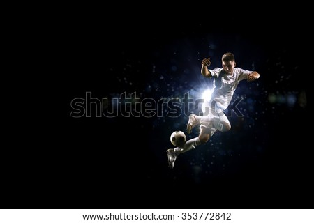 Soccer player in the air over black background - stock photo