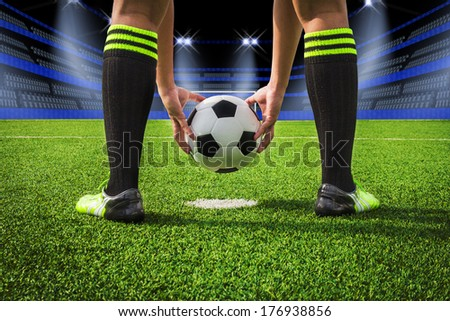 soccer player paste ball on green grass field at night in stadium; penalty - stock photo