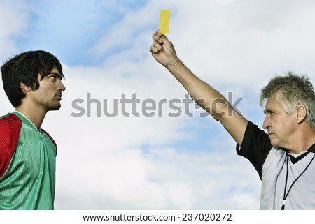 Soccer Player Receiving Yellow Card - stock photo