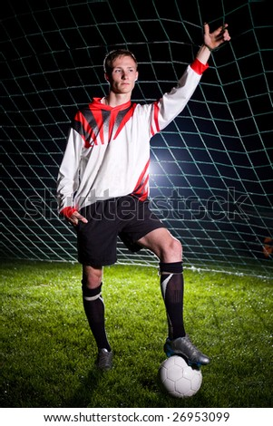 soccer player relaxing in the dark stadium - stock photo