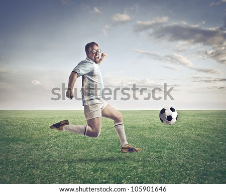 Soccer player running after a football on a meadow - stock photo