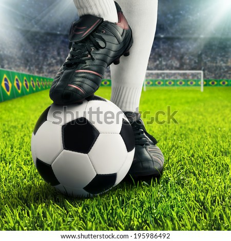 Soccer player's feet in casual pose in a football arena, with the crowd in the background - stock photo