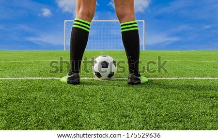 Soccer player's feet on field, with sky in background - stock photo