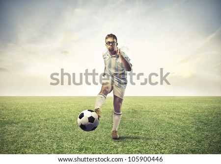 Soccer player shooting a football on a meadow - stock photo