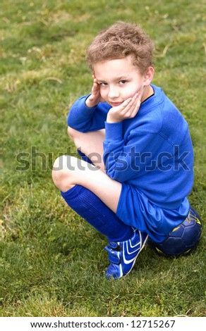 Soccer player sitting on ball on sideline - stock photo