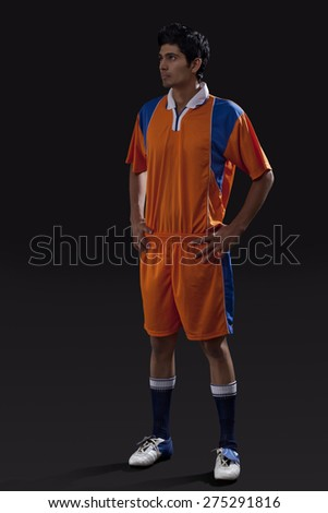 Soccer player standing with hands on hip as he looks away isolated over black background - stock photo