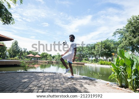 Soccer player training in front of pool - stock photo