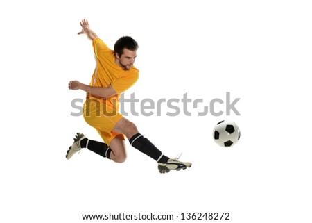 Soccer player wearing a yellow uniform kicking the ball on a white background - stock photo