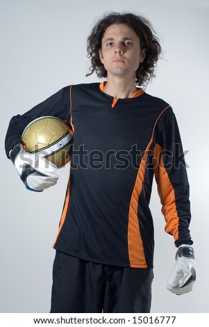 Soccer player wearing goalie gloves and a jersey holds a soccer ball and has an angry look on his face. Vertically framed photograph - stock photo