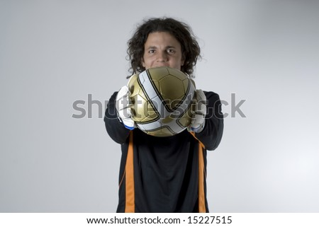 Soccer player wearing goalie gloves holds soccer ball out in front of him. Horizontally framed photograph - stock photo