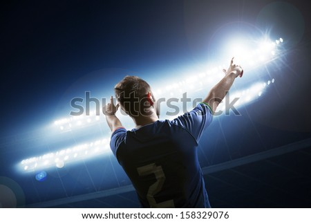 Soccer player with arms raised cheering - stock photo